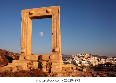 Portara gate with moon and city of Naxos, Greece.