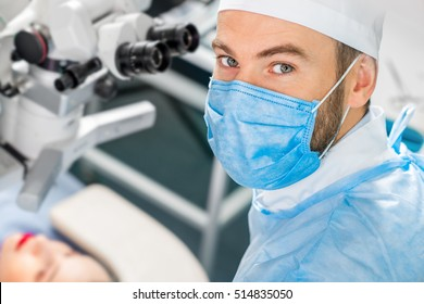 Portarit of eye surgeon at the working plase near the microscope in the operating room