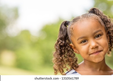 Portarit of a mixed race little girl laughing and smiling.