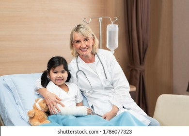 Portarit of smaile doctor pediatrician and little girl patient on bed with teddy bear