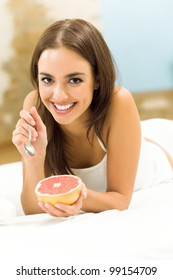 Portarit of young happy smiling beautiful woman eating grapefruit on bed, at home
