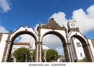 Portas da Cidade Gates and San Sabastian church with a clock tower in Ponta Delgada, Azores, Portugal. Azores capital city attractions under cloudy skies.