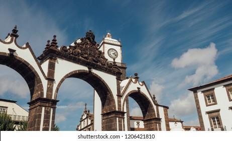 Portas da Cidade to the village of Ponta Delgada in Azores, Portugal. Entrance gates and the clock tower of Saint Sabastian church.
