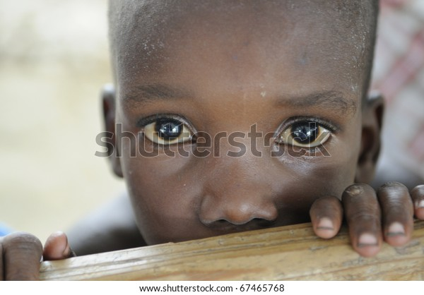 PORT-AU-PRINCE - AUGUST 22: An unidentified poor Haitian kid looking with surprise towards the photographer during a food camp ,in Port-Au-Prince, Haiti on August 22, 2010.