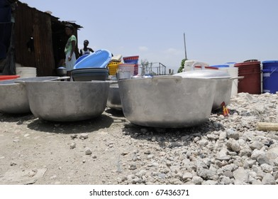 PORT-AU-PRINCE - AUGUST 25:  Residents of Cite Soleil- one of the poorest and dangerous slum area in the Western Hemisphere drying utensils, in Port-Au-Prince, Haiti on August 25, 2010.