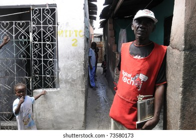 PORT-AU-PRINCE - AUGUST 25: A vendor standing with a wireless phone to provide residents  a chance to call their loved ones after the earthquake in Cite Soleil,in Port-Au-Prince,Haiti on August 25,2010