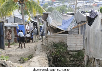 PORT-AU-PRINCE - AUGUST 28: Children and the adults passing their time by playing cards or  outdoor games in on of the Tent City on August 28, 2010 in Port-Au-Prince, Haiti
