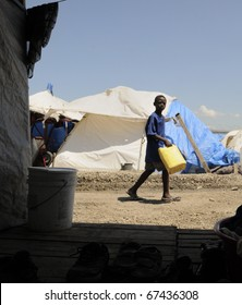 PORT-AU-PRINCE - AUGUST 28: A Haitian unidentified kid going pass a tent to collect water for his family for a day , in Port-Au-Prince, Haiti on August 28, 2010.