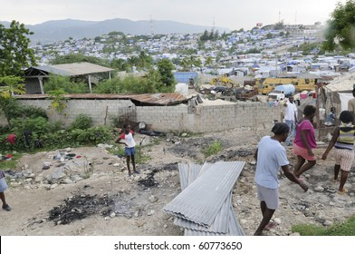 PORT-AU-PRINCE - AUGUST 28:  Residents gathering their belongings after their tents was destroyed due to fire, on August 28, 2010 in Port-Au-Prince, Haiti