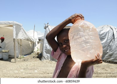 PORT-AU-PRINCE - AUGUST 28: An unidentified young boy carrying a bottle of water after the water arrived in the tent city ,in  Port-Au-Prince, Haiti on August 28, 2010.