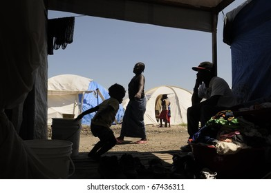 PORT-AU-PRINCE - AUGUST 28:  A woman carrying water for her daily needs as seen from inside a tent, in Port-Au-Prince, Haiti on August 28, 2010.
