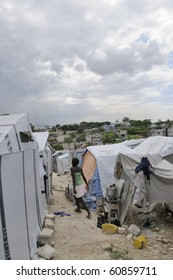 PORT-AU-PRINCE - AUGUST 28:   A young girl going inside her tent while cooking outside in one of the tent cities  in Port-Au-Prince, Haiti on August 28, 2010.