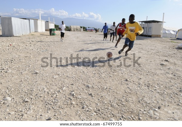 PORT-AU-PRINCE - AUGUST 30:  Haitian teenagers playing soccer in the tent camps , a favorite sport of the Haitians,  in Port-Au-Prince, Haiti on August 30, 2010.