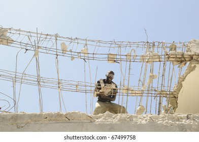 PORT-AU-PRINCE - AUGUST 30:  An Haitian worker using a sledge hammer to break down the  skeleton of a building  in Port-Au-Prince, Haiti on August 30, 2010.