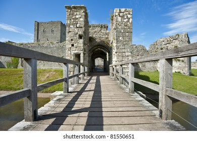 Portchester Castle in Hampshire viewed over a wooden bridge on a beautiful day