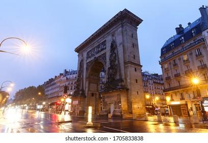 The Porte Saint-Denis triumphal arch at rainy night . Built in 1672 and designed by architect Francois Blondel. Paris. France.