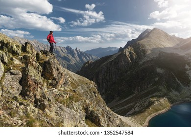 Porter of a bearded traveler hipster in sunglasses and a cap with a backpack and trekking poles stands on a high cliff near the cliff on the background of epic mountains of rocks and clouds
