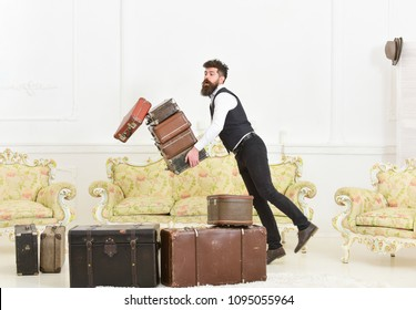 Porter, butler accidentally stumbled, dropping pile of vintage suitcases. Baggage insurance concept. Man with beard and mustache in classic suit delivers luggage, luxury white interior background