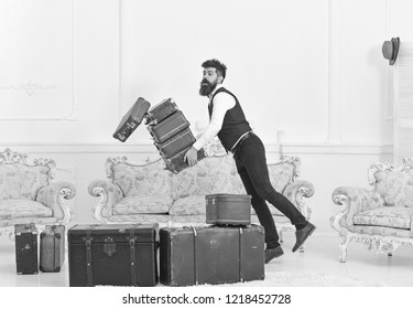 Porter, butler accidentally stumbled, dropping pile of vintage suitcases. Baggage insurance concept. Man with beard and mustache in classic suit delivers luggage, luxury white interior background.