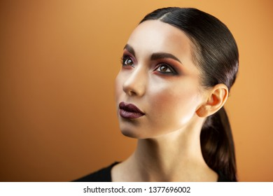 porter Eurasian girl with smooth hair and clear skin, on an orange background, exquisite make-up having hidden her head looks up
