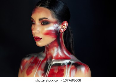 porter Eurasian girls with dark hair on a black background conceptual makeup silver black and red shades