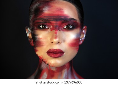 Porter Eurasian girls with dark hair and clear skin, and brown eyes, on a black background, in makeup red ottenkami on the face in the form of strokes, and delicate red lips