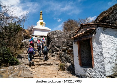 Porter pass through Mani stones on the way to Everest base camp, Nepal, Mani stones are stone plates, rocks or pebbles, inscribed with the six syllabled mantra of Avalokiteshvara (Om ma ni pad me hum)