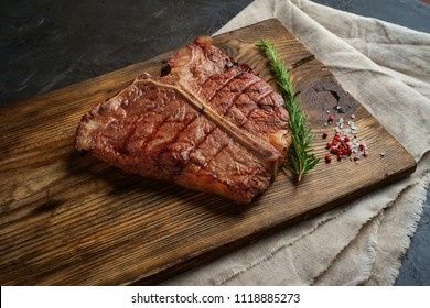 Porterhouse beef steak cooked on a grill on a wooden Board