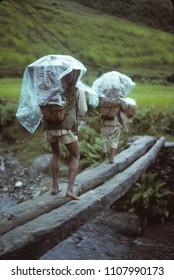 Porters carrying loads across a bridge across a narrow gorge, Khumbu Himalaya,Nepal, Asia