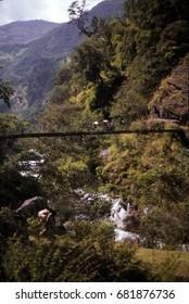 Porters carrying loads across a suspension bridge across a narrow gorge, Khumbu Himalaya,Nepal, Asia