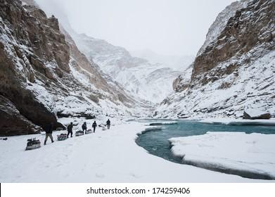 Porters walking on the frozen Zanskar River (Chadar Trek) in Ladakh, India