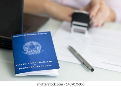 """A portfolio of Brazilian workers (Translation """"Work Permit, Ministry of Labor and Social Security Brazil CTPS""""), female hand stamping a work contract background"""