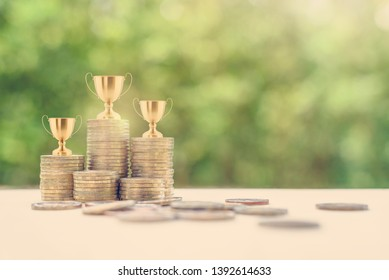 Portfolio management champion / money or asset investment winner, financial concept : Golden trophy on rows of rising coins, depicts great performance a manager manage a portfolio for highest profit