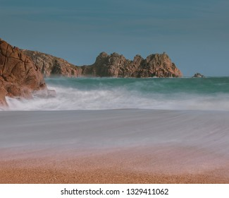 Porthcurno beach cornwall and Logan Rock in the distance