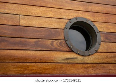 A porthole in an old vintage style on a historic sailing boat. Warm tinted wooden materials creating a retro feeling