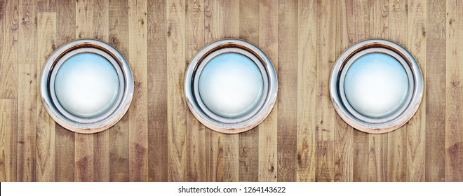 Porthole on the old nautical vessel. Ship's portholes as three round holes at wooden background for your marine cruise or sea voyage. Metal bronze windows frame on the yacht or at pirate ship.