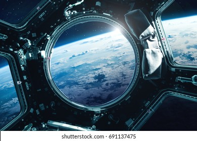 Porthole of space station near the Earth on the background. Elements of this image furnished by NASA