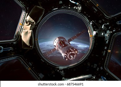 Porthole of space station and space ship in the outer space. Earth sunshine on the background. Elements of this image furnished by NASA