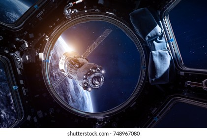 Porthole of space station and space ship in the outer space. Earth sunshine on the background. Space wallpaper. Elements of this image furnished by NASA