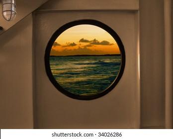 Porthole View of an ocean isle sunset through a round porthole