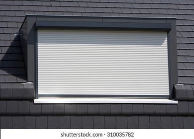 Porthole with a white rolling shutter on a black roof