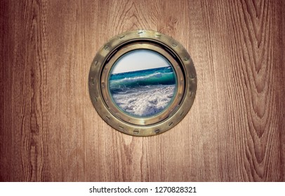 Porthole window on board of the old ship and view on sea waves - look an ocean during a storm. Brass porthole frame on the wooden wall of a sailboat for your story about a sea cruise or travelling.