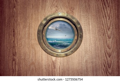 Porthole window on a board of the ship - view on ocean waves during a storm with flying seagulls. Brass porthole frame on the wooden wall of a sailboat for your story about a sea cruise or travelling.