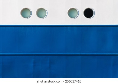 Portholes in white and blue ship's side, one is different, emergency exit
