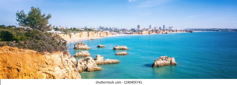Portimao, city on the Atlantic coast at sunset, red cliffs and sandy beach, Beautiful seascape, Algarve, Portugal, panoramic banner view