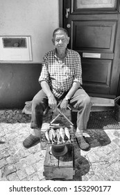 PORTIMAO, PORTUGAL - AUGUST 3: A local man cooks sardines outside his house whilst wearing his slippers on AUGUST 3, 2013 in Portimao, PORTUGAL.