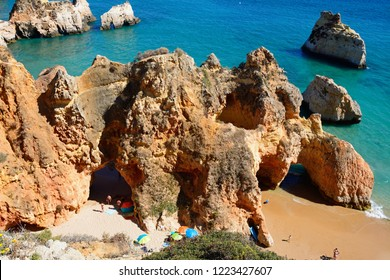 PORTIMAO, PORTUGAL - JUNE 10, 2017 - Elevated view of the cliffs with tourists relaxing on a secluded beach, Praia da Rocha, Portimao, Algarve, Portugal, Europe, June 10, 2017.