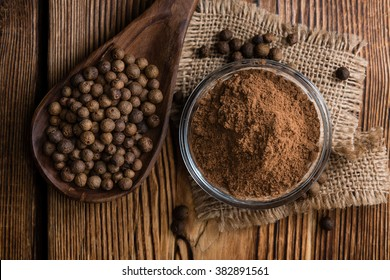 Portion of Allspice powder (detailed close-up shot) on wooden background