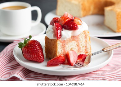 Portion of angel food cake served with whipped cream and strawberries