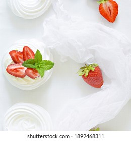 Portion australian dessert Pavlova with airy butter cream, fresh strawberries and mint on a white plate.